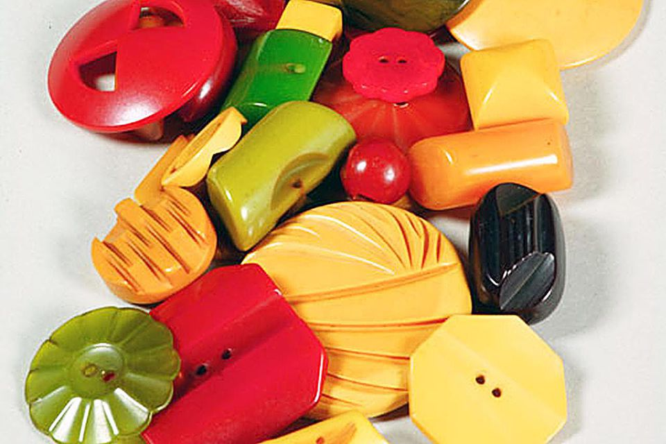 24 Bakelite buttons of various shapes, sizes, and colors; colors include different shades of green, red, white, and amber; some have brass fasteners.