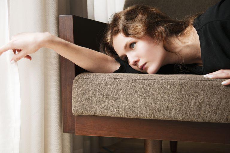 Woman lying on sofa, touching net curtain