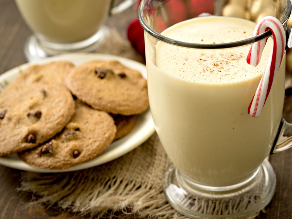 Glass of egg nog next to a plate of cookies
