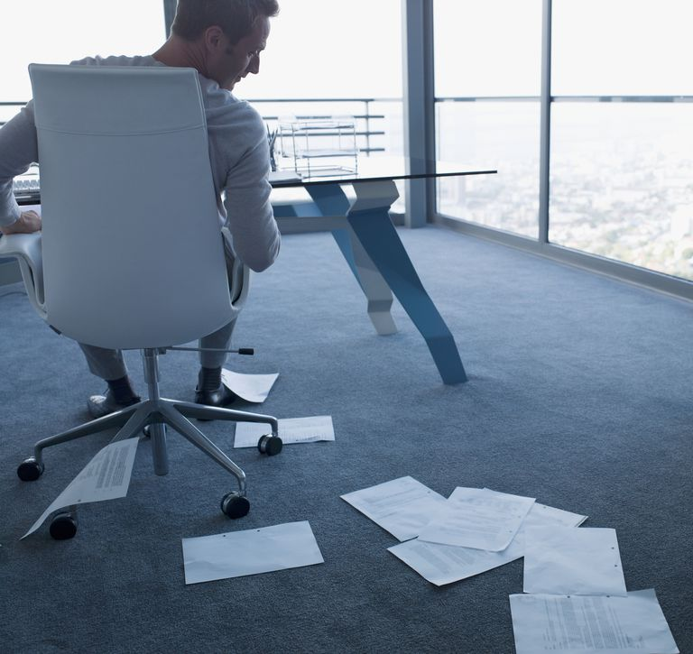 Businessman looking at paperwork on office floor