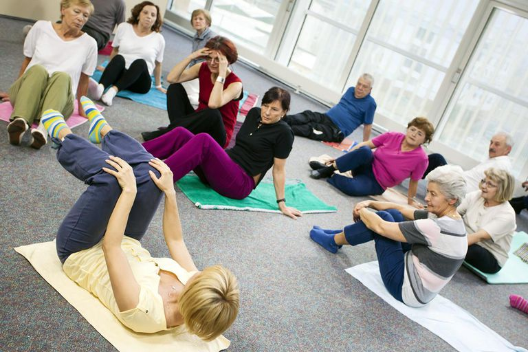 Group of adults sitting on the floor and listening female pilates instructor.