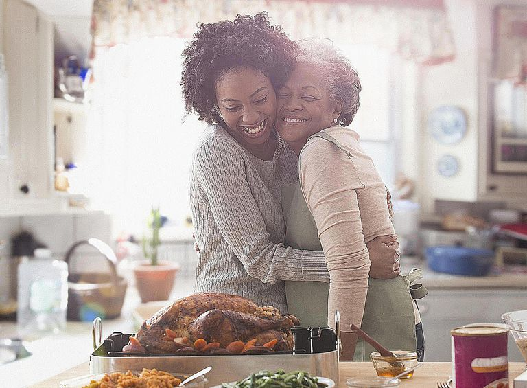 A mother and daughter hug and beam with happiness while preparing Thanksgiving dinner together.
