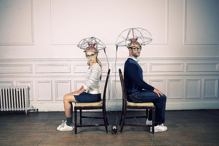 A man and woman sit in chairs with electrical measurements on their heads, indicative of conditions in a controlled experiment.