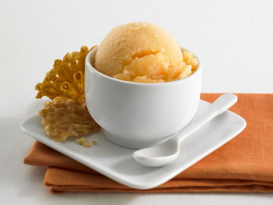 orange sherbet in a cup with a cookie on the side
