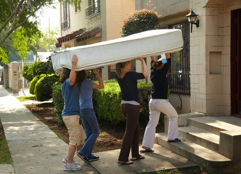 4 women carry mattress while moving
