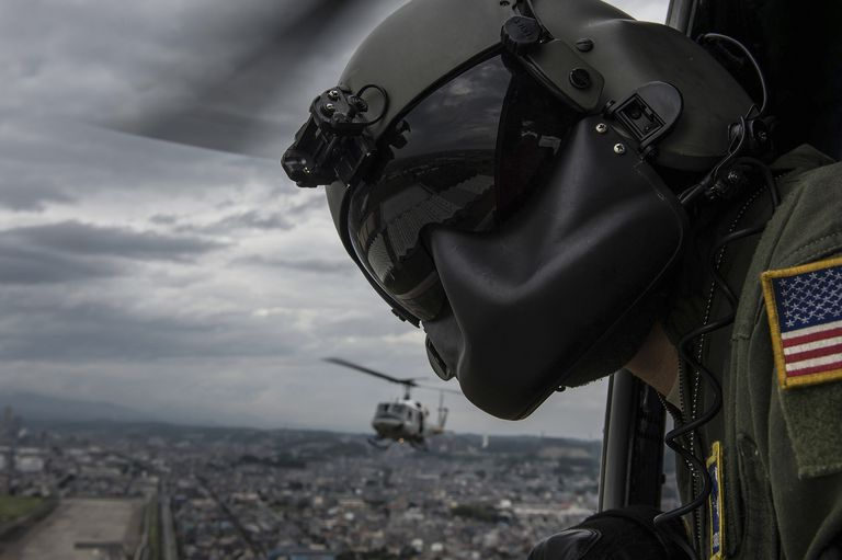 Crew chief scans the area from a UH-1N Huey helicopter.