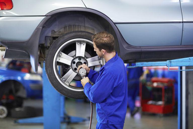 Auto repairman installing tires on car