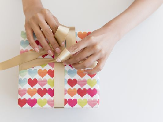 Woman wrapping up a Valentine's Day Gift.
