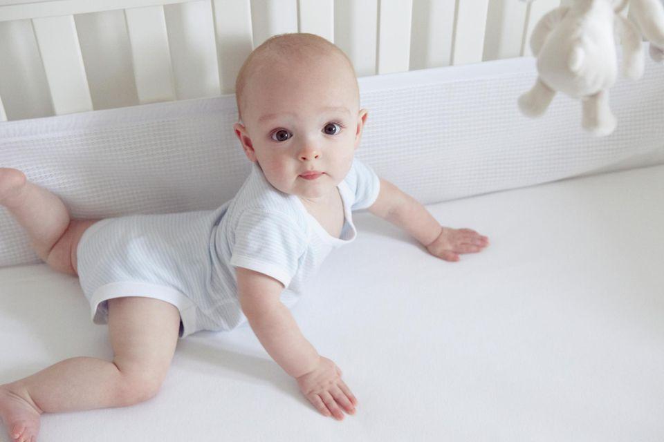 Baby boy crawling in crib with mesh crib bumpers