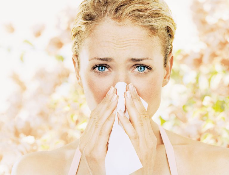 Woman with allergies blowing her nose.