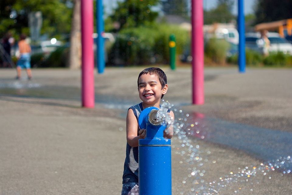 Happy boy spraying water at water park.