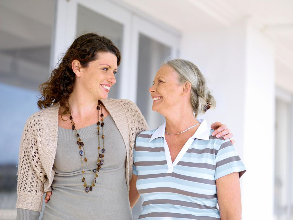 Mature woman with adult daughter, smiling at each other