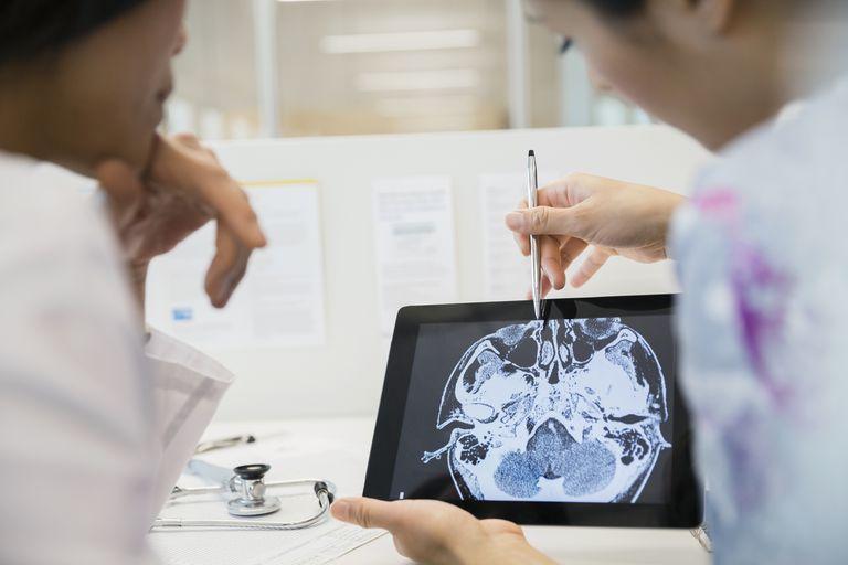 Doctor and nurse examining CT scan digital tablet