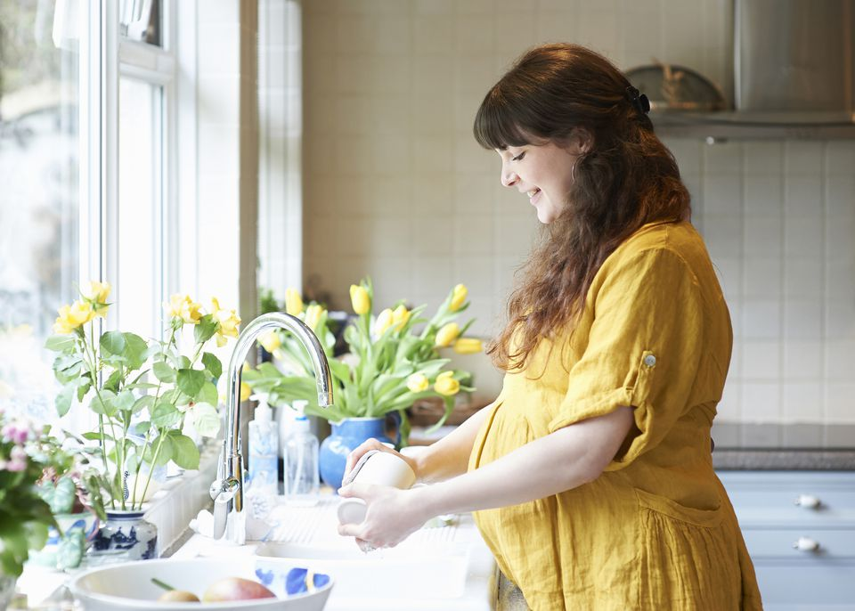 Profile of pregnant woman washing dishes at home.