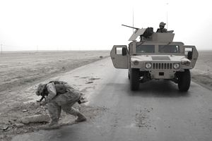 US Marine checks a pothole for mines on Main Supply Route Tin, during a convoy from Camp Al Asad to Al Qaim, during Operation Iraqi Freedom.