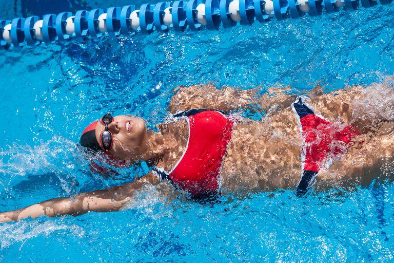 Woman with red bikini swimming in pool.
