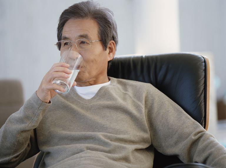 senior Asian man drinking water