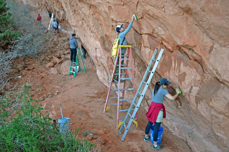 olunteers with the Pikes Peak Climbing Alliance scrub white chalk off boulder problems
