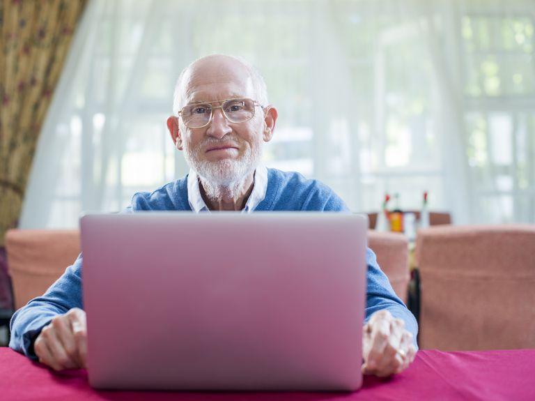 Confident senior man with laptop