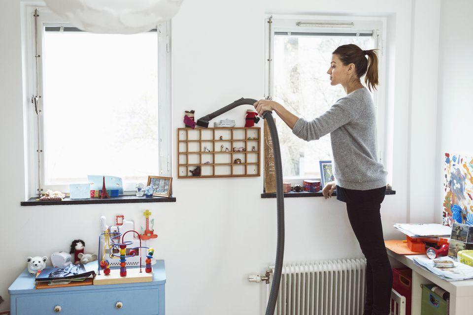 Woman vacuuming small shelves