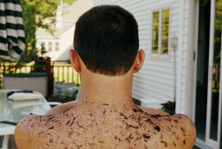 Bare chested man with hair cut from head on back