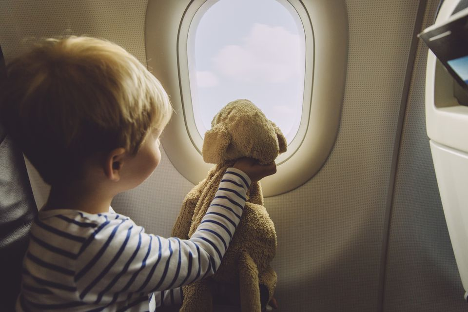 Little boy sitting on an airplane with his soft toy looking through window