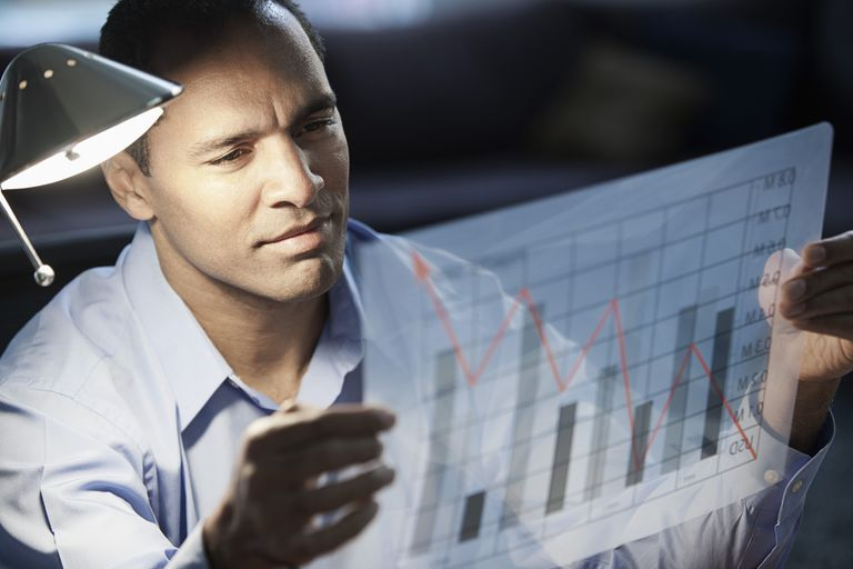 Mixed race businessman looking at bar graph