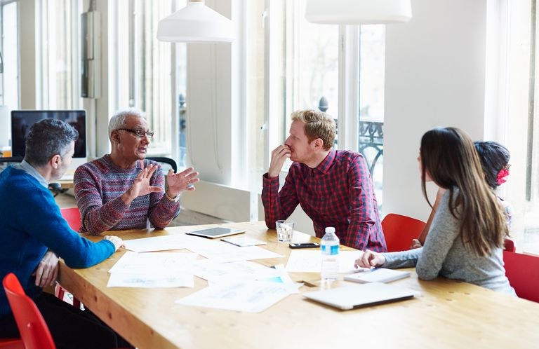 Coworkers discussing a project at conference table