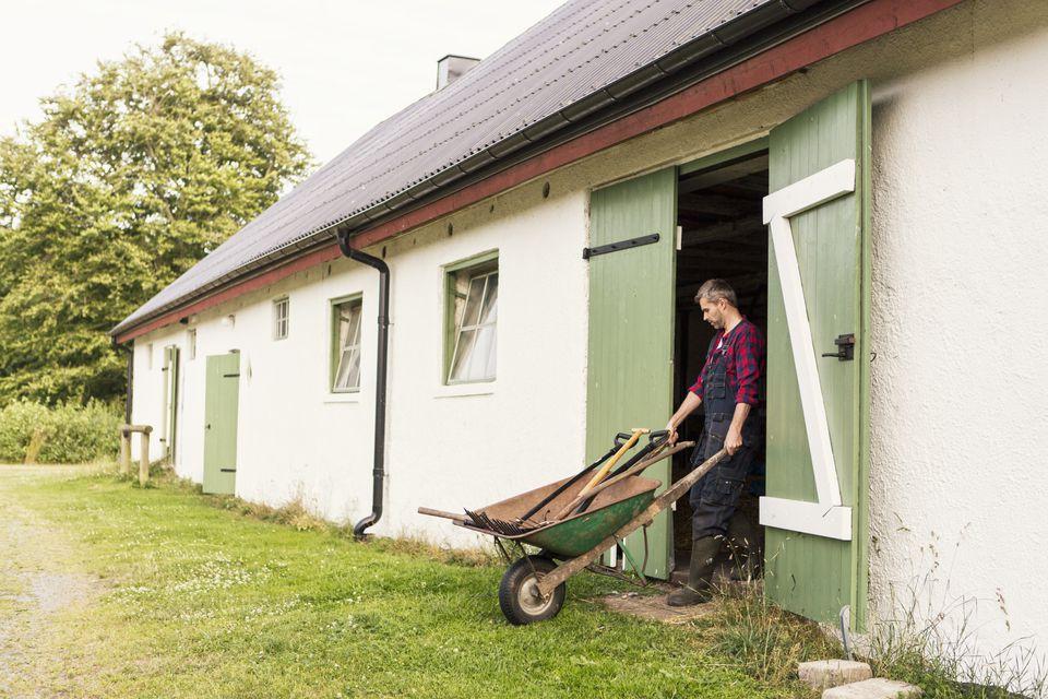 Man pushing wheelbarrow while coming out of barn at farm