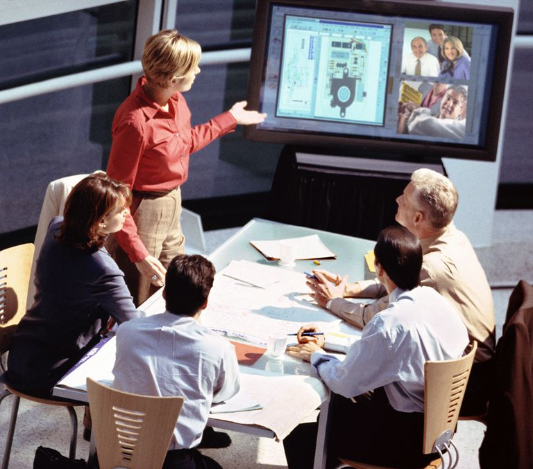 Business executives in meeting, woman pointing at monitor, elevated