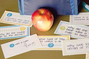 Lunch box notes besides a lunch bag and an apple.