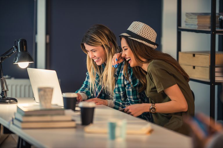 2 women laughing at computer