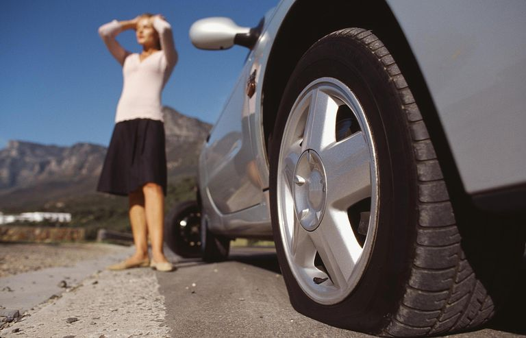 Close-up of car with flat tire and young woman with hands on his head