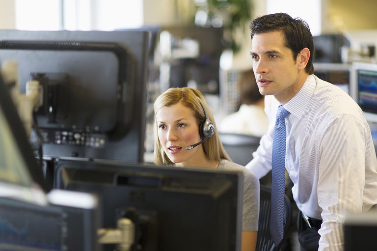male and female stock traders in front of computer