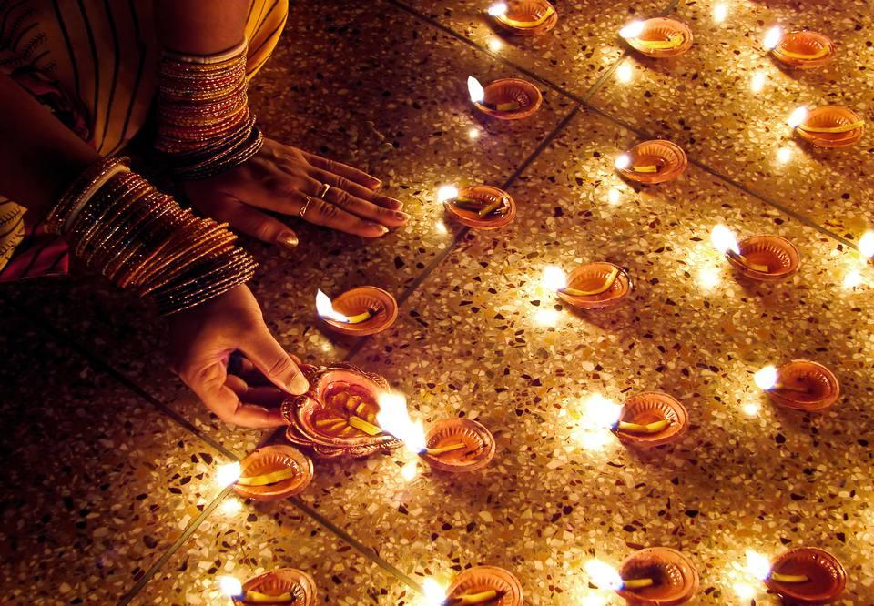 A woman's hand lighting Diwali diyas