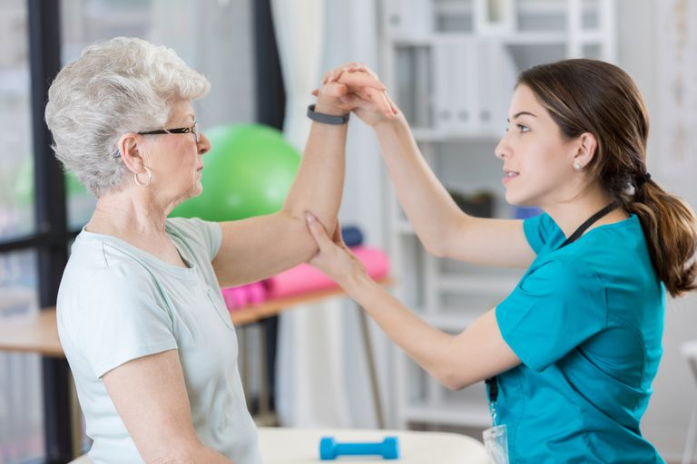 Physical therapist helps woman raise arm