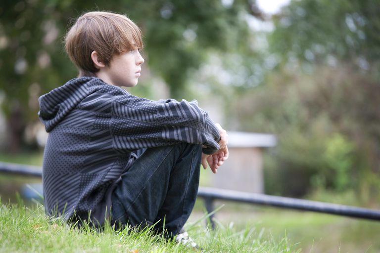 Young Boy Sitting on Hillside