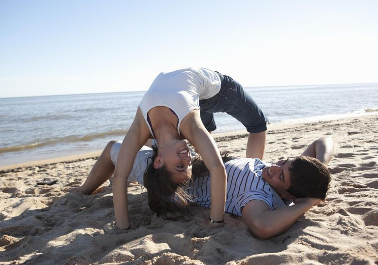Woman doing back bend over man at the beach