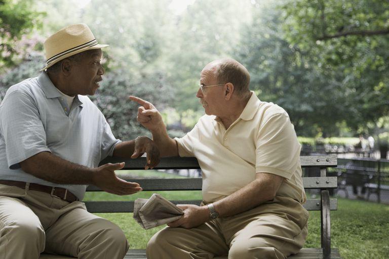 Men arguing on park bench