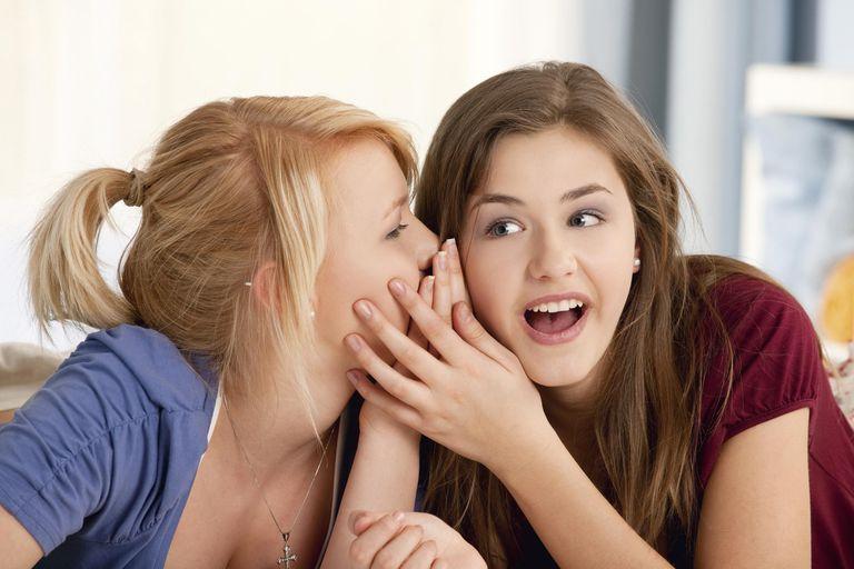 Two teenage girls whispering