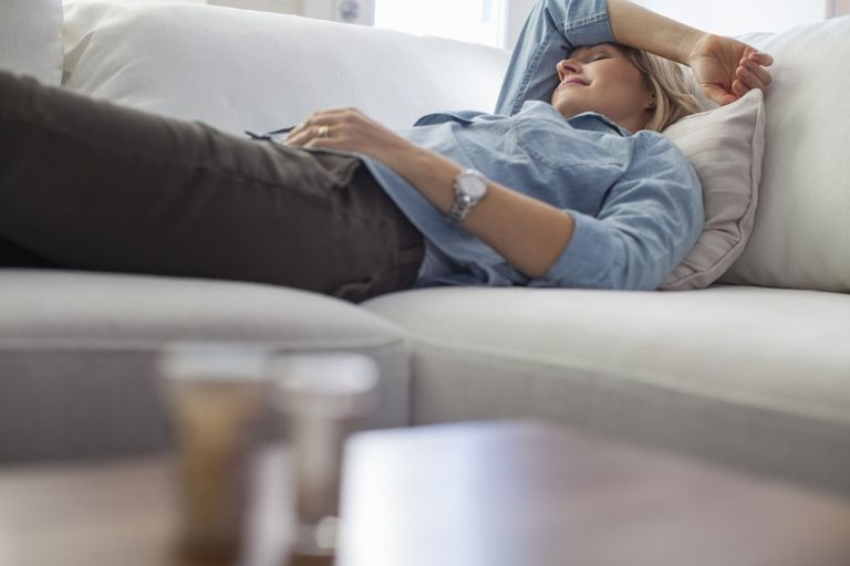 Woman sleeping on couch with migraine.