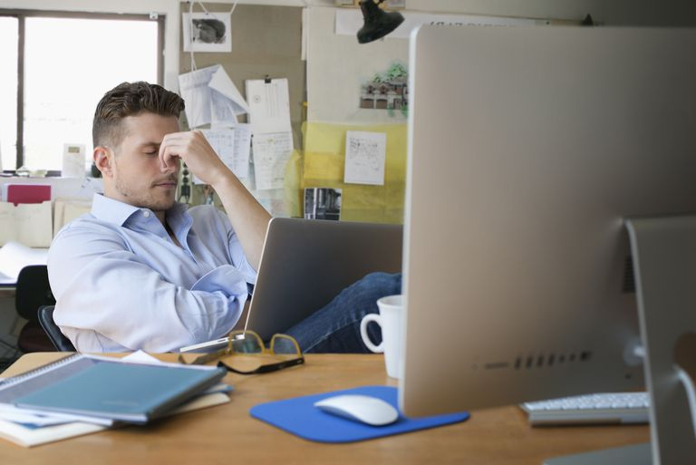 Frustrated Caucasian businessman with laptop in office