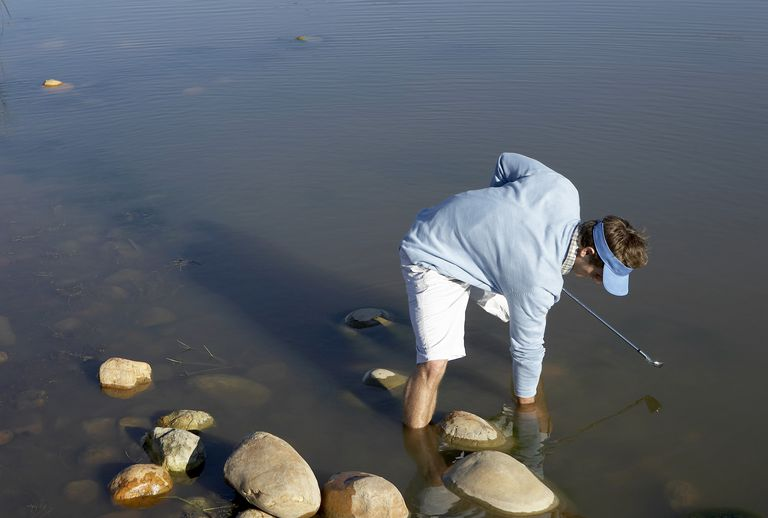 Man searching for golf ball lost in water hazard