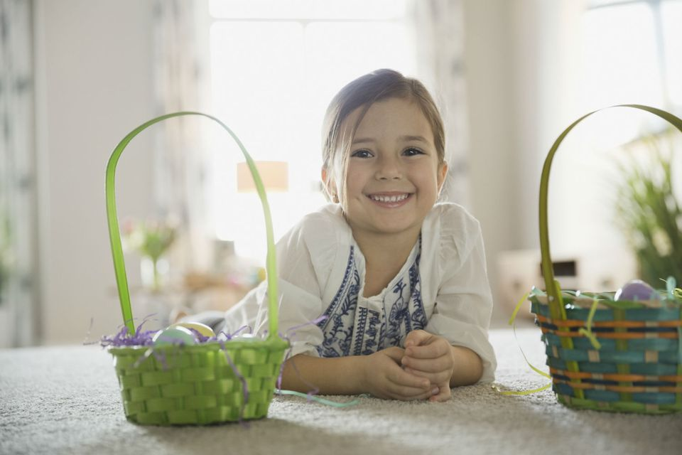 A young girl flanked by a pair of Easter baskets