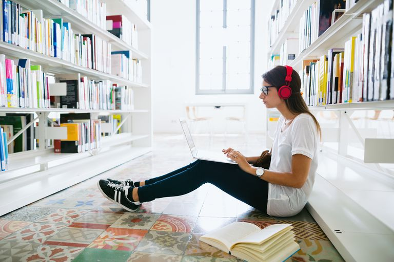 Woman listening to music on headphones in library