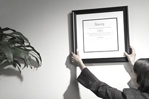 Financial advisor hanging credentials on their office wall.