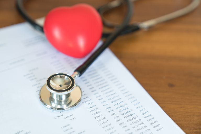 Medical bills in background with stethoscope and red heart