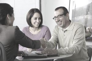 Saleswoman shaking hands with Hispanic couple