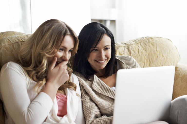 Women using laptop and laughing