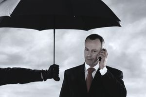 Man holding umbrella over businessman using mobile phone